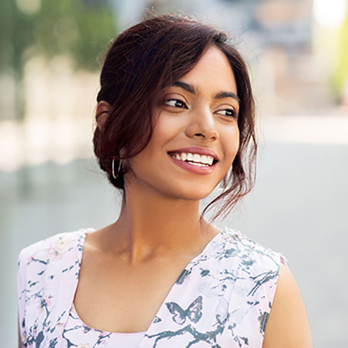 young woman with big smile outside